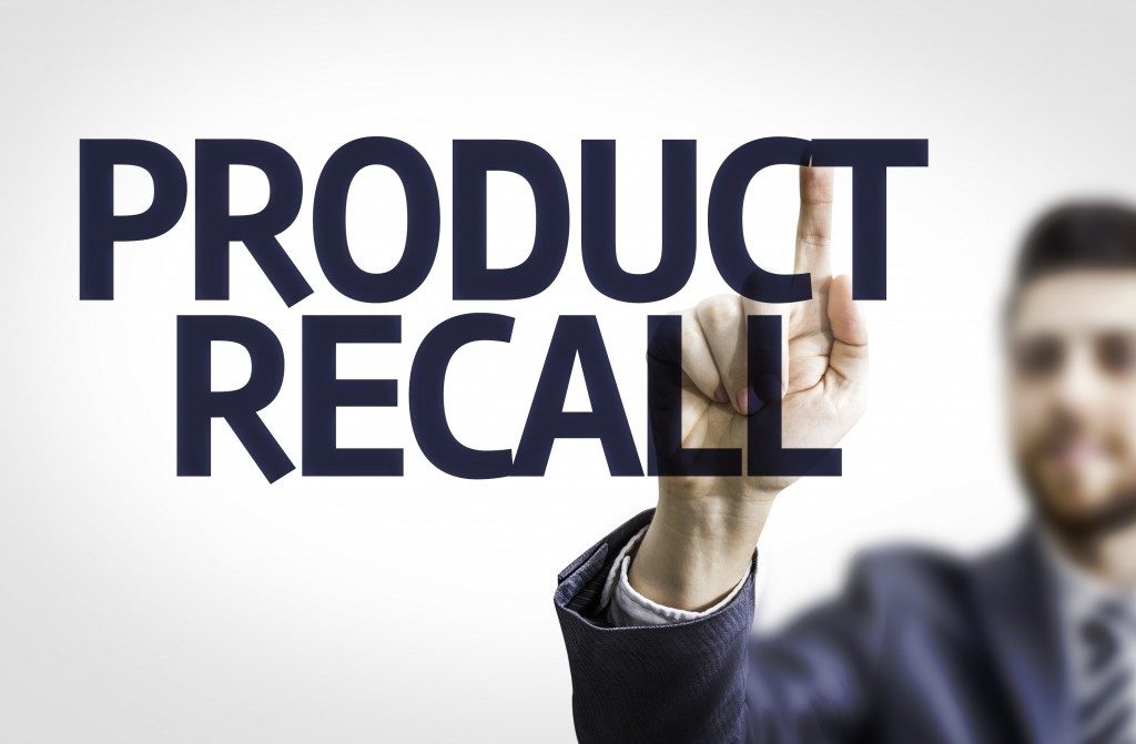 Business man pointing to transparent board with text: Product Recall