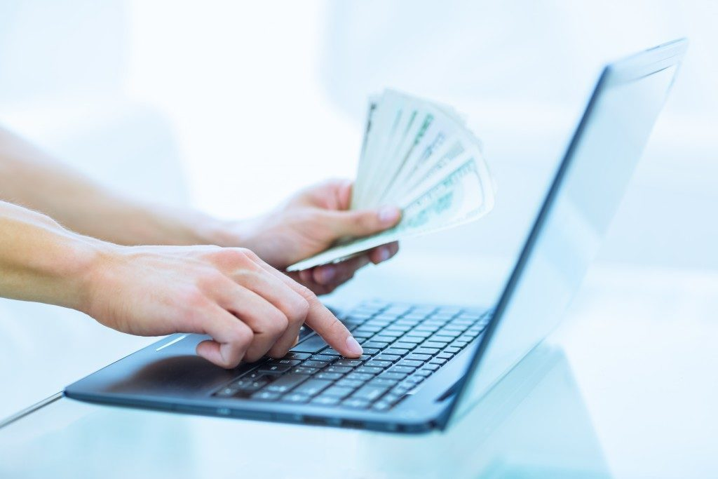 Person holding money while using a laptop