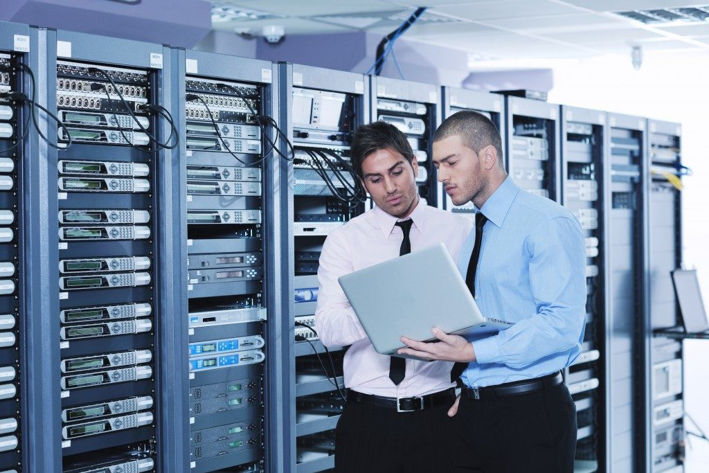 2 technicians looking at laptop in the server room