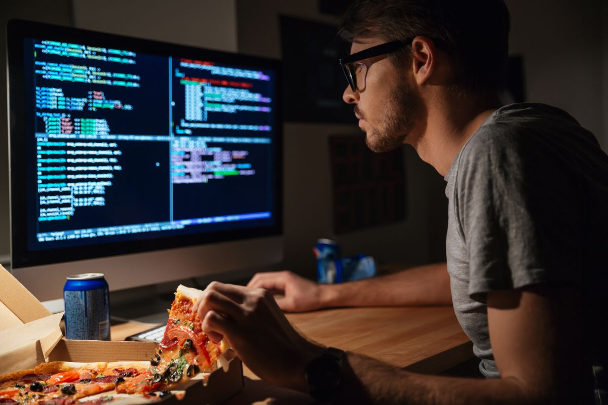 man holding pizza while working on coding