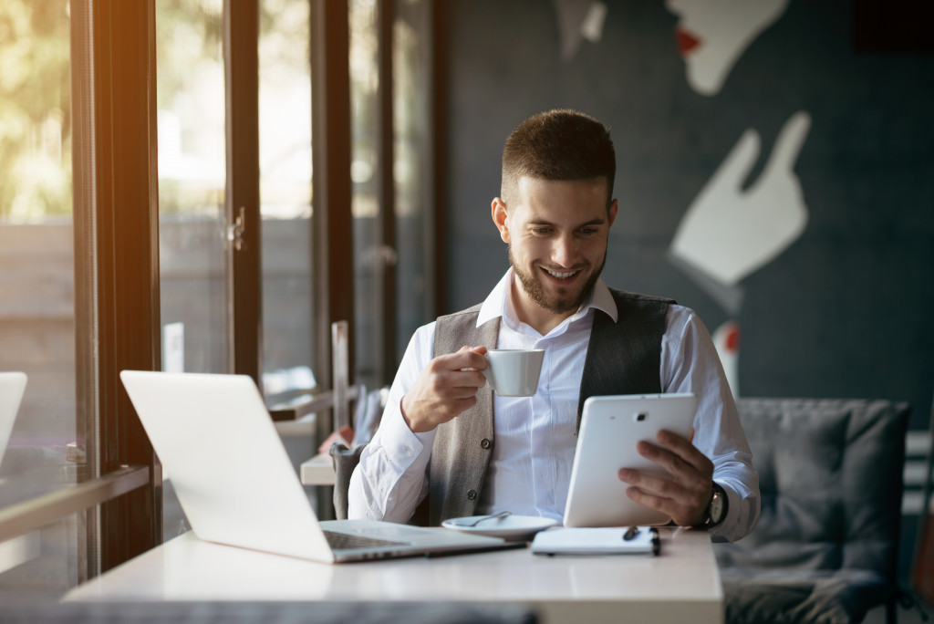 man holding tablet and coffee